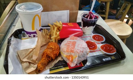 Kuala Lumpur, Malaysia -  26 March 2019 : Varieties of McDonald's food.  A fried chicken, burger, french fries,  ice-cream and a drinks on a table.