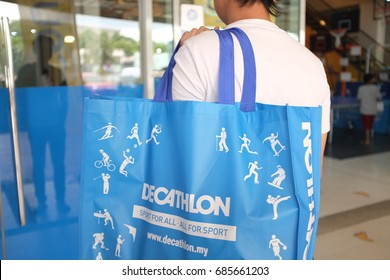 Kuala Lumpur, Malaysia - 27 July 2018 : Shopper holding Decathlon shopping bag. Decathlon is a chain of store opened in France in 1976 and one the world's leading sporting goods.