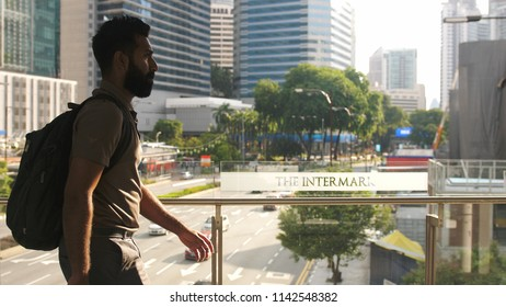 Kuala Lumpur, Malaysia, 28 june 2018. Young businessman with backpack walking on pedestrian crossing on a busy day in the center of the city on a sunny day on the road on the background.