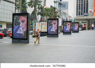 Kuala Lumpur, Malaysia - 3 December 2017 : Unknown muslim woman walking near the digital advertising boards installed at the Pavilion shopping centre  in Kuala Lumpur city centre.