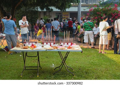 KUALA LUMPUR, MALAYSIA, 8 MAR 2014: Table with various ancestor offerings setup by chinese family members at Kwong Tong cemetary, a chinese burial site during the qingming or tomb sweeping day.