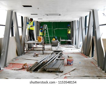 KUALA LUMPUR, MALAYSIA -APRIL 06, 2017: Construction site workers are doing ceiling soffit skim coat work at the construction site. Two layers base and final coat apply to get the smooth surface.