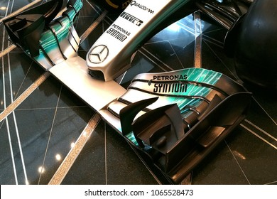 KUALA LUMPUR, MALAYSIA - APRIL 08, 2018: A tourists looking on replica Mercedes-AMG Petronas Motorsport F1 racing car displayed at the entrance of KLCC Shopping mall.