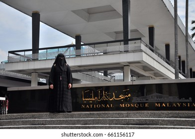KUALA LUMPUR, MALAYSIA - APRIL 1, 2017: An islamic woman is standing in front of National Mosque of Malaysia (Masjid Negara), Kuala Lumpur, Malaysia. This mosque was declared open on 1965.