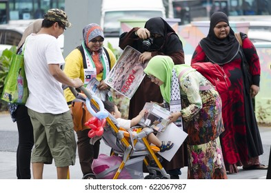 KUALA LUMPUR, MALAYSIA. APRIL 12 2015. child and parent giving a donation to a volunteer for syria