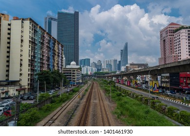 Kuala Lumpur, Malaysia - April 12th, 2019 : City of Bangsar landmark, train KTM railway, overlooking famous Menara TM or TM tower with dramatic blue sky.