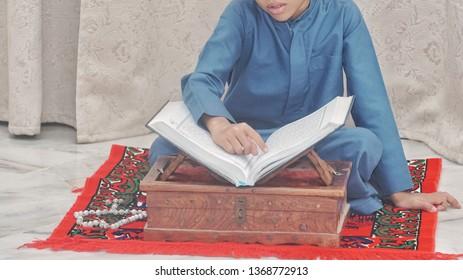 Kuala Lumpur, Malaysia - April 2019: Young muslim boy reciting Quran in the holy month of Ramadan