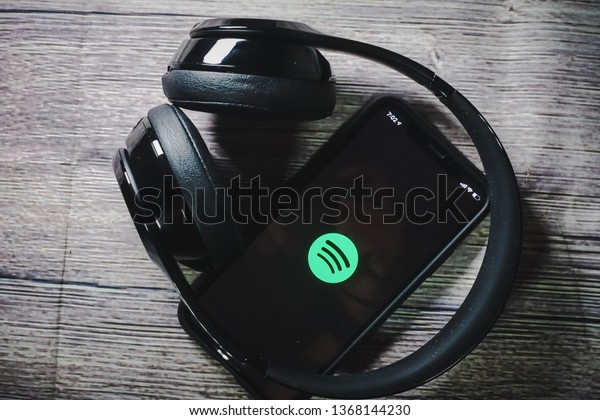 Kuala Lumpur, Malaysia - April 2019. An iphone XS screen showing spotify icon with beats earphone, perfect for listening musics on the go