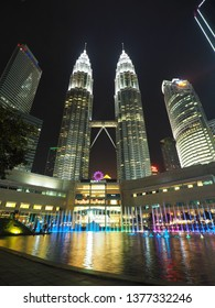 Kuala Lumpur / Malaysia - April 3, 2019 : Beautiful night scenery of Petronas Twin tower and Suria KLCC with color ful fountain and reflection in the pool.
