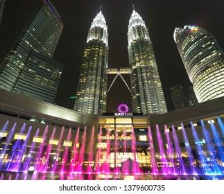 Kuala Lumpur / Malaysia - April 3, 2019 : Beautiful night scenery of Petronas Twin tower and Suria KLCC with colorful pink, purpke and blue fountain.