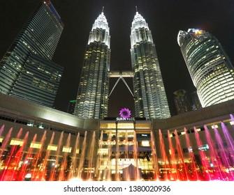 Kuala Lumpur / Malaysia - April 3, 2019 : Beautiful night scenery of Petronas Twin tower and Suria KLCC with colorful orange and pink fountain.