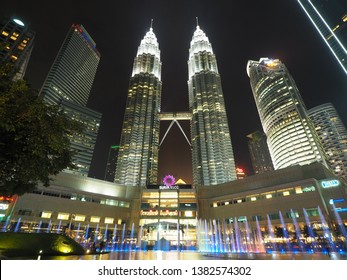 Kuala Lumpur / Malaysia - April 3, 2019 : Beautiful night scenery of Petronas Twin tower and Suria KLCC with colorful fountain and reflection in the pool.
