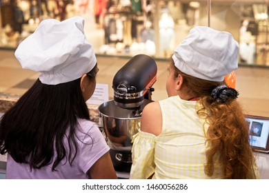 Kuala Lumpur, Malaysia - August 1 2018: Two young girls enjoy a baking session during school holidays using Kitchen Aid mixer.