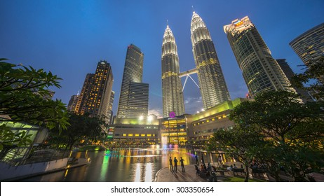 KUALA LUMPUR, MALAYSIA - AUGUST 1, 2015: Water Fountain at Suria KLCC with Petronas Towers and Office Buildings at Blue Hour sunset at Night. It's a popular shopping attraction to locals and tourists.