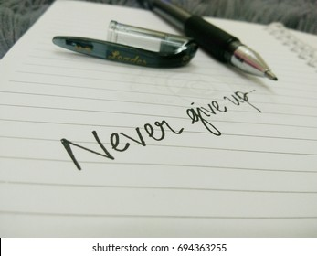 "KUALA LUMPUR, MALAYSIA - AUGUST 10, 2017 : Motivational quote ""Never give up"" written on book using black ball pen."