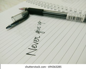 """KUALA LUMPUR, MALAYSIA - AUGUST 10, 2017 : Motivational quote """"Never give up"""" written on book using black ball pen."""