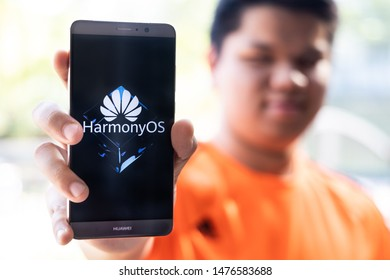 KUALA LUMPUR, MALAYSIA, August, 11, 2019: Huawei officially announced its new operating system, HarmonyOS. Illustrative of person holding Huawei smart phone with HarmonyOS on screen.
