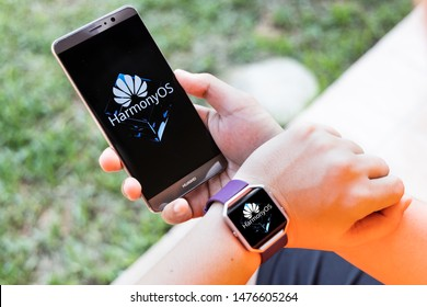 KUALA LUMPUR, MALAYSIA, August, 11, 2019: Huawei officially announced its new operating system, HarmonyOS. Illustrative of person wearing smart watch and smart phone with HarmonyOS on screen