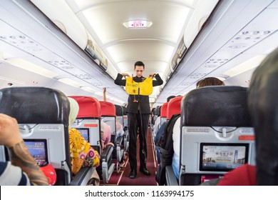 KUALA LUMPUR, MALAYSIA - August 20, 2018: Series of steward demonstrating safety procedure prior to commercial Airasia airline flight took off.