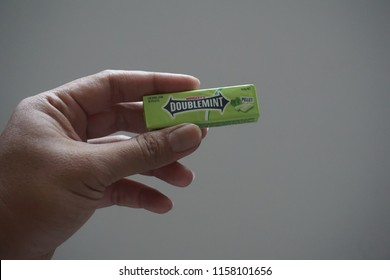 KUALA LUMPUR, MALAYSIA - AUGUST 2018 :Closeup hand holding Wrigley's Doublemint chewing gum. Manufactured by Wrigley Company, the chewing gum are currently sold in more than 180 countries worldwide.