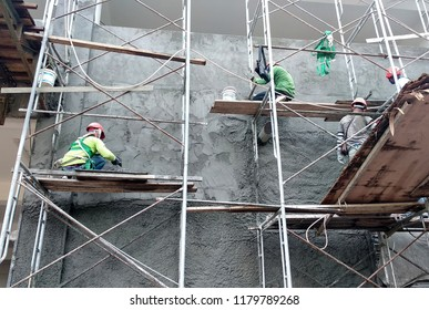 KUALA LUMPUR, MALAYSIA -AUGUST 23, 2018: Brick wall plastered by construction workers using the cement plaster. Scaffolding used as temporary staging to work at height. Wearing appropriate safety gear