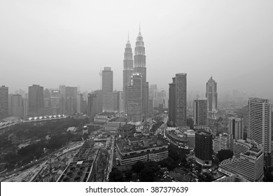 KUALA LUMPUR, MALAYSIA - AUGUST 25, 2015: Kuala Lumpur skyline with the Petronas Twin Towers on a hazy evening. The haze is caused by Indonesian forest fires. Photo in black and white.