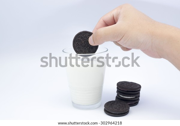KUALA LUMPUR, MALAYSIA - AUGUST 3rd 2015. Hand holding Oreo Cookies dunk to glass of milk. Oreo is a sandwich cookie with a sweet cream is the best selling cookie in the US.