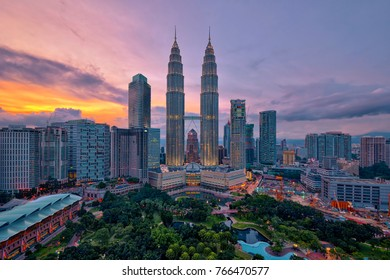 Kuala Lumpur, MALAYSIA - circa August 2017: Petronas Twin Towers (fondly known as KLCC) and the surrounding buildings at sunset seen from the Skybar at Traders Hotel.