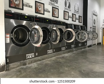 Kuala Lumpur, Malaysia, circa December 2018 - a row of mashing machines in a self service laundry shop