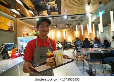 KUALA LUMPUR, MALAYSIA - CIRCA JANUARY, 2020: indoor portrait of worker at McDonald's restaurant in Kuala Lumpur.