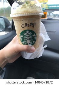 Kuala Lumpur, Malaysia- Circa July 2019. Delicious Frappucino drink from famous food and beverage restaurants 'Starbuck' holding by women in the car.
