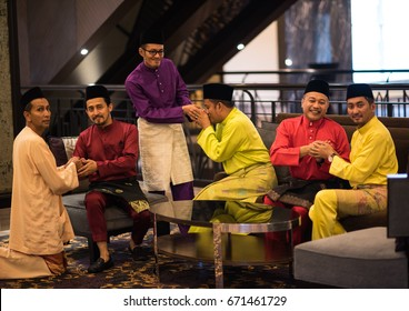 Kuala Lumpur, Malaysia - Circa July 2016 - A portrait shot of good friends wearing colorful traditional Malay male attire asking for forgiveness during Eid at the end of the month of Ramadan