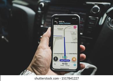 Kuala Lumpur, Malaysia - Circa September 2019 : A hand holding an iphone x with a Waze navigation application open inside a car. Selective focus