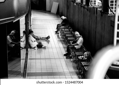 Kuala Lumpur, Malaysia - Circa September 2019: A group of homeless elderly Chinese resting in an empty lane in Pudu Plaza. Black and white