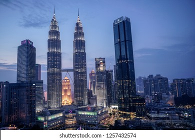 Kuala Lumpur, Malaysia – Dec 11 2018 : Petronas Twin Towers (fondly known as KLCC) and the surrounding buildings during sunset seen from the Skybar at Traders Hotel.