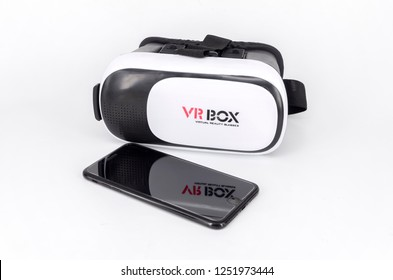 Kuala Lumpur, Malaysia - December 07, 2018; Packshot image of Apple iPhone and virtual reality headset (VR Box) on white background. Selective focus.