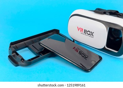 Kuala Lumpur, Malaysia - December 07, 2018; Packshot image of Apple iPhone and virtual reality headset (VR Box) on blue background. Selective focus.