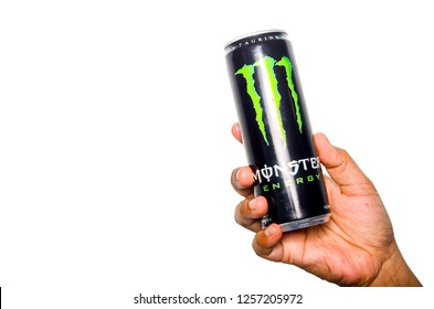 Kuala Lumpur, Malaysia - December 12, 2018; Hand hold can of Monster energy drink on white background. Introduced in 2002 Monster now has over 30 different drinks with high a caffeine content.