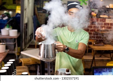 Kuala Lumpur, Malaysia, December 20, 2018: At the famous Jalan Alor night street food market a stall holder prepares an ice confection containing liquid nitrogen which produces  Dragon Breath effect