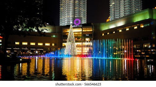 KUALA LUMPUR, MALAYSIA - DECEMBER 7: Night scene of Petronas Twin towers Suria KLCC colorful dancing fountain with music with Christmas tree at the back in Kuala Lumpur, Malaysia on December 7, 2016