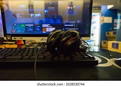 Kuala Lumpur, Malaysia - FEB 19th 2018: Headphone over the keyboard in cyber cafe with dota 2 on the screen.