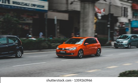 Kuala Lumpur, Malaysia - Feb 23 2019: Panning Shot of red Volkswagen Golf driving along the road in KL