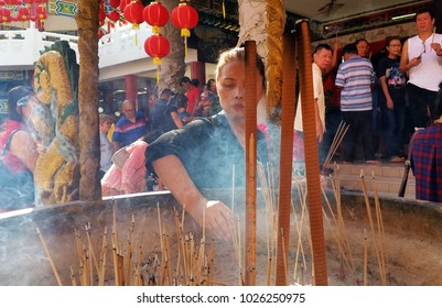 Kuala Lumpur, Malaysia - February 16, 2018: Woman burn incense sticks and pray for good fortune during Chinese New Year Day in Thean Hou Temple.