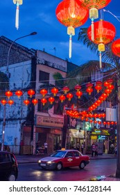 KUALA LUMPUR, MALAYSIA - FEBRUARY 16, 2013: A red taxi passes under glowing red Chinese New Year lanterns on a downtown city street on a dark, rainy night.
