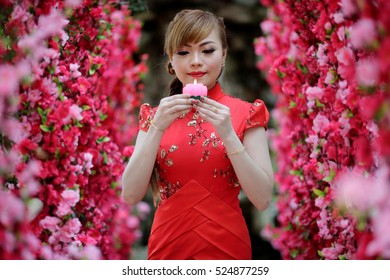 KUALA LUMPUR, MALAYSIA - FEBRUARY 18, 2015: A Chinese girl, Anne Chan, 26 years old, carrying a lotus candle after she offering a prayer surrounded by red flowers at Thean Hou Temple, Kuala Lumpur.