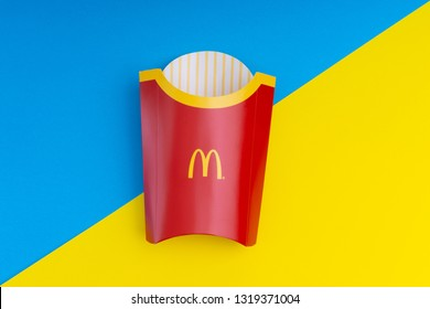 KUALA LUMPUR MALAYSIA - FEBRUARY 20, 2019: McDonald's fries paper bags on blue and yellow background with selective focus