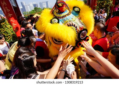 KUALA LUMPUR, MALAYSIA - FEBRUARY 2019 : People do not miss the opportunity to touch and give Ang Pow during Chinese New Year Lion Dance performances at Thean Hou Temple.