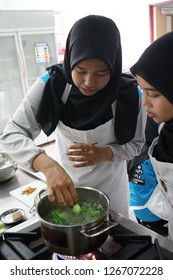 Kuala Lumpur, Malaysia - February 22, 2018:  Good friends laughing and talking while preparing meals at table full of vegetables and pasta ready for cooking in kitchen.