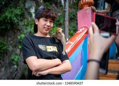 Kuala Lumpur, Malaysia - February 26, 2019: Unknown tourist smiles at camera with monkey on his shoulder.