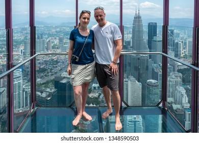 Kuala Lumpur, Malaysia - February 26, 2019: Caucasian tourists in Sky Box on KL tower enjoy the view to the Petronas Towers.